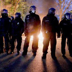 Berlín: Agentes de policía se paran frente a un fuego durante una manifestación de grupos de izquierda.   Foto:Christoph Soeder / DPA