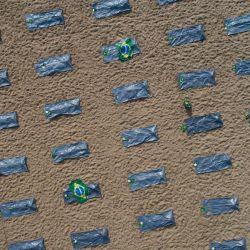 Brasil, Río de Janeiro: Bolsas para cadáveres yacen simbólicamente en la playa de Copacabana para las víctimas de la pandemia del coronavirus, mientras miembros de la ONG    Foto:Fernando Souza / DPA