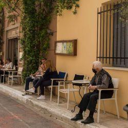Grecia, Atenas: la gente se sienta en un café en el distrito de Monastiraki con la Acrópolis al fondo. Grecia relaja las medidas impuestas a causa de la pandemia de Coronavirus.   Foto:Socrates Baltagiannis / DPA