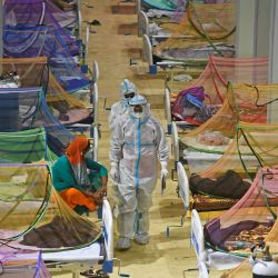 Los trabajadores de la salud que usan trajes de equipo de protección personal (PPE) asisten a pacientes con coronavirus Covid-19 dentro de un centro de la aldea de los Juegos de la Commonwealth convertida temporalmente en un centro de atención de Covid, en Nueva Delhi.   Foto:Tauseef Mustafa / AFP