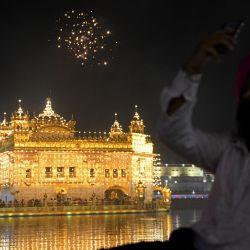 Un devoto sij toma fotografías de fuegos artificiales con motivo del aniversario del nacimiento de Guru Arjan Dev en el Templo Dorado iluminado en Amritsar.   Foto:Narinder Nanu / AFP