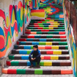 Un niño palestino sentado en escalones decorados con colores vibrantes en el barrio al-Daraj de la ciudad de Gaza.   Foto:Mohammed Abed / AFP