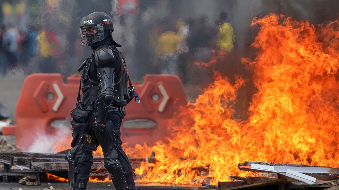 A riot policeman is seen next to dire during clashes following a protest against a tax reform bill launched by Colombian President Iván Duque, in Cali, Colombia on April 29, 2021.