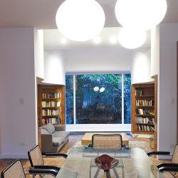 A un costado del comedor se ubica una biblioteca que también juega con las curvas y termina en un gran ventanal repleto de verde.