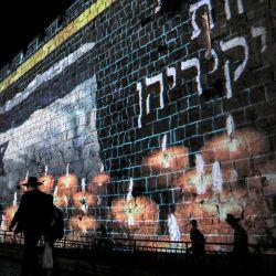 Una proyección de una bandera israelí ondeando antes de velas encendidas se muestra en las murallas de la ciudad vieja de Jerusalén, cuando Israel declara un día nacional de luto por las víctimas de una estampida durante las vacaciones de Lag BaOmer en el Monte Meron. | Foto:Ahmad Gharabli / AFP