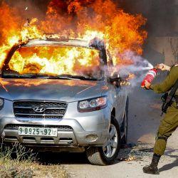 Un soldado israelí intenta apagar las llamas en un vehículo palestino en llamas durante una operación de seguridad en la aldea de Aqraba, al este de Nablus, en la ocupada Cisjordania. | Foto:Jaafar Ashtiyeh / AFP