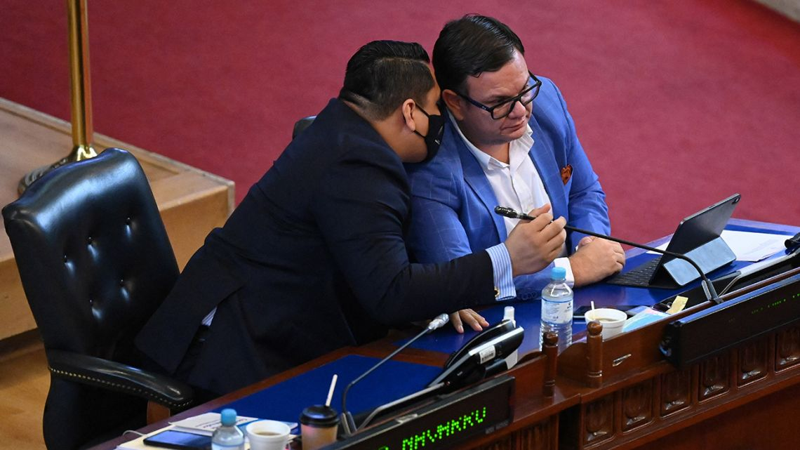 Deputies Caleb Navarro (L) and Christian Guevara, of the New Ideas ruling party, speak during the second plenary session of the Salvadoran Legislative Assembly, which majority is pro-government, in San Salvador, on May 5, 2021
