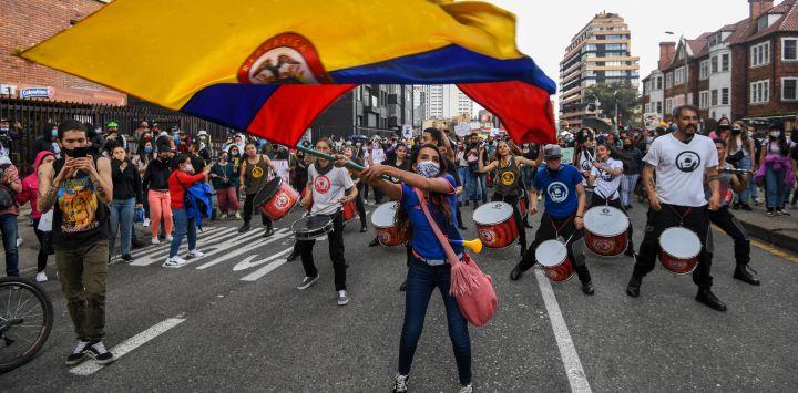 Una mujer ondea una bandera nacional de Colombia durante una protesta contra una reforma tributaria propuesta por el gobierno del presidente colombiano Iván Duque en Bogotá.