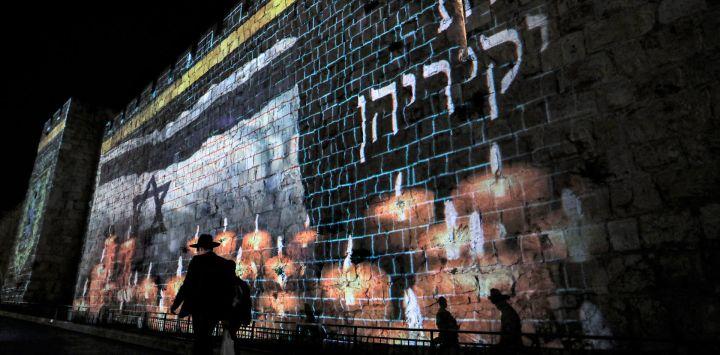 Una proyección de una bandera israelí ondeando antes de velas encendidas se muestra en las murallas de la ciudad vieja de Jerusalén, cuando Israel declara un día nacional de luto por las víctimas de una estampida durante las vacaciones de Lag BaOmer en el Monte Meron.