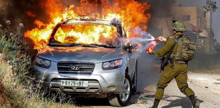 Un soldado israelí intenta apagar las llamas en un vehículo palestino en llamas durante una operación de seguridad en la aldea de Aqraba, al este de Nablus, en la ocupada Cisjordania.