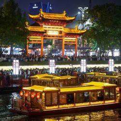Esta foto muestra a personas en botes mientras visitan Fuzimiao, también llamado Templo Confuciano, en Nanjing, en la provincia oriental de Jiangsu, en China. | Foto:STR / AFP