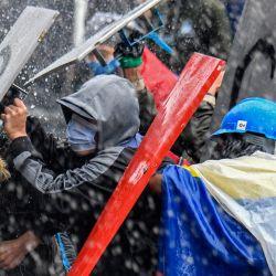 Manifestantes chocan con la policía antidisturbios durante una protesta contra el gobierno del presidente Iván Duque en la plaza Bolívar de Bogotá. | Foto:Juan Barreto / AFP