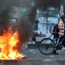 Un manifestante pasa junto a una barricada en llamas que bloquea una calle durante una protesta contra el gobierno del presidente Iván Duque en Cali, Colombia. | Foto:Luis Robayo / AFP