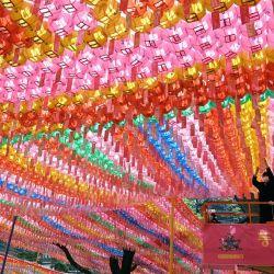 Un trabajador del templo coloca tarjetas con los deseos de los seguidores budistas en linternas de loto en el templo Jogye en Seúl, antes de las celebraciones que marcan el cumpleaños de Buda en Corea del Sur. | Foto:Jung Yeon-je / AFP