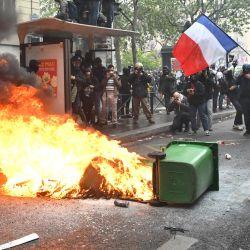 Los manifestantes se paran cerca de un cubo de basura en llamas en la calle durante la manifestación en París. | Foto:Bertrand Guay / AFP
