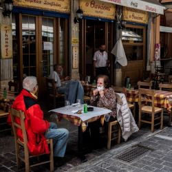 La gente se sienta en la terraza de un restaurante en la plaza Monastiraki en Atenas, mientras los restaurantes y cafés en Grecia abren después de seis meses de cierre debido a la pandemia de Covid-19. | Foto:Angelos Tzortzinis / AFP