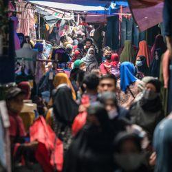 Esta fotografía muestra a personas comprando ropa en los puestos callejeros de Yakarta. | Foto:Bay Ismoyo / AFP