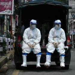 El ejército de Nepal usa trajes de equipo de protección personal (PPE) en un vehículo mientras esperan para transportar el cuerpo de una persona que murió por el coronavirus Covid-19 a un crematorio en Katmandú. | Foto:Prakash Mathema / AFP