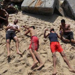 Nadadores palestinos yacen en la playa después de participar en un campeonato de salvavidas organizado por el ministerio del gobierno local con la policía naval. El campeonato se lleva a cabo para seleccionar un salvavidas en preparación para la temporada de verano. | Foto:Ashraf Amra / APA Imágenes a través de ZUMA Wire / DPA