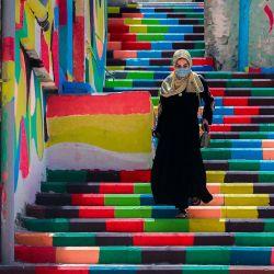 Una mujer palestina, con una máscara protectora en medio de la pandemia de COVID-19, baja las escaleras decoradas con colores vibrantes en el barrio al-Daraj de la ciudad de Gaza. | Foto:Mohammed Abed / AFP