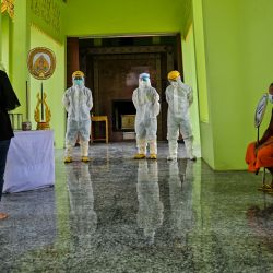 Los monjes budistas y los voluntarios de rescate de la fundación Siam Nonthaburi supervisan el funeral de una mujer, que murió después de contraer el coronavirus Covid-19, mientras su hija (izquierda) rinde sus últimos respetos en el crematorio del templo budista Wat Rat Prakhong Tham en Nonthaburi. | Foto:Lillian Suwanrumpha / AFP