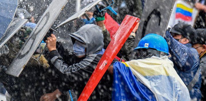 Manifestantes chocan con la policía antidisturbios durante una protesta contra el gobierno del presidente Iván Duque en la plaza Bolívar de Bogotá.