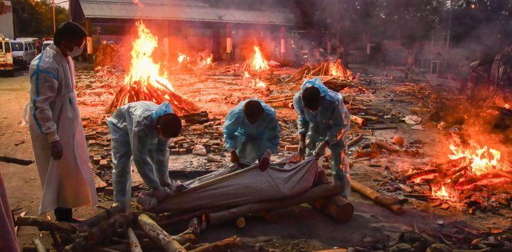 Texto original India, Nueva Delhi: personas llevan a cabo una cremación masiva de cuerpos de personas que murieron por complicaciones del coronavirus en un crematorio improvisado en medio de una ola de infecciones sin precedentes que actualmente se extiende por India.