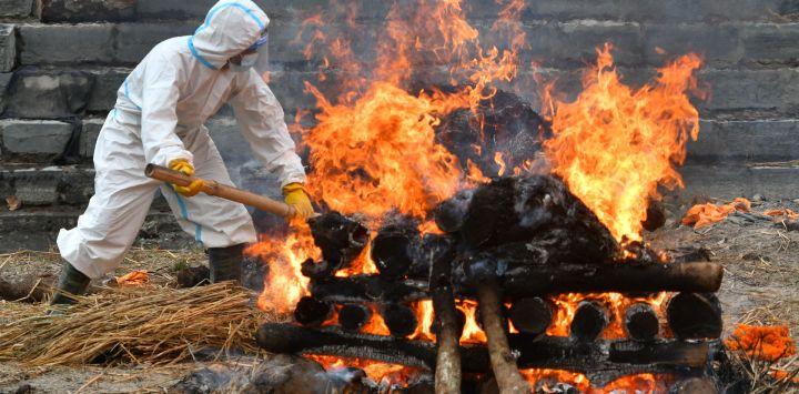 Un hombre vestido con un traje de equipo de protección personal (EPP) revisa una pira funeraria de una persona que murió debido a la enfermedad del coronavirus Covid-19, en un campo de cremación en Katmandú.