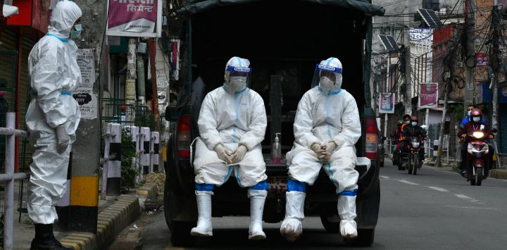 El ejército de Nepal usa trajes de equipo de protección personal (PPE) en un vehículo mientras esperan para transportar el cuerpo de una persona que murió por el coronavirus Covid-19 a un crematorio en Katmandú.