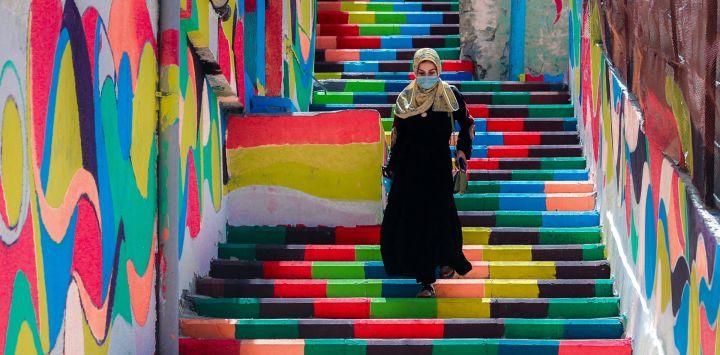 Una mujer palestina, con una máscara protectora en medio de la pandemia de COVID-19, baja las escaleras decoradas con colores vibrantes en el barrio al-Daraj de la ciudad de Gaza.