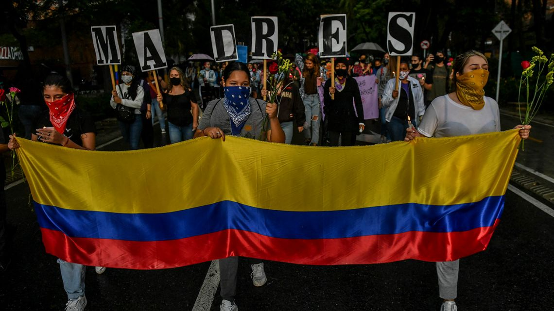 """Women hold a Colombian flag and the letters forming the word """"Mothers"""" during a protest against President Ivan Duque's government, in Medellin, Colombia, on May 6, 2021. Colombia's government on Thursday invited protest leaders to a dialogue in an attempt to calm tensions following more than a week of deadly demonstrations against President Ivan Duque."""