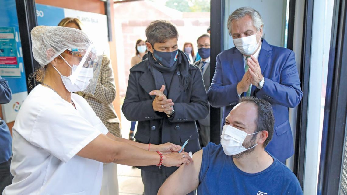 Buenos Aires Province Governor Axel Kicillof applauds as a citizen is vaccinated against Covid-19.