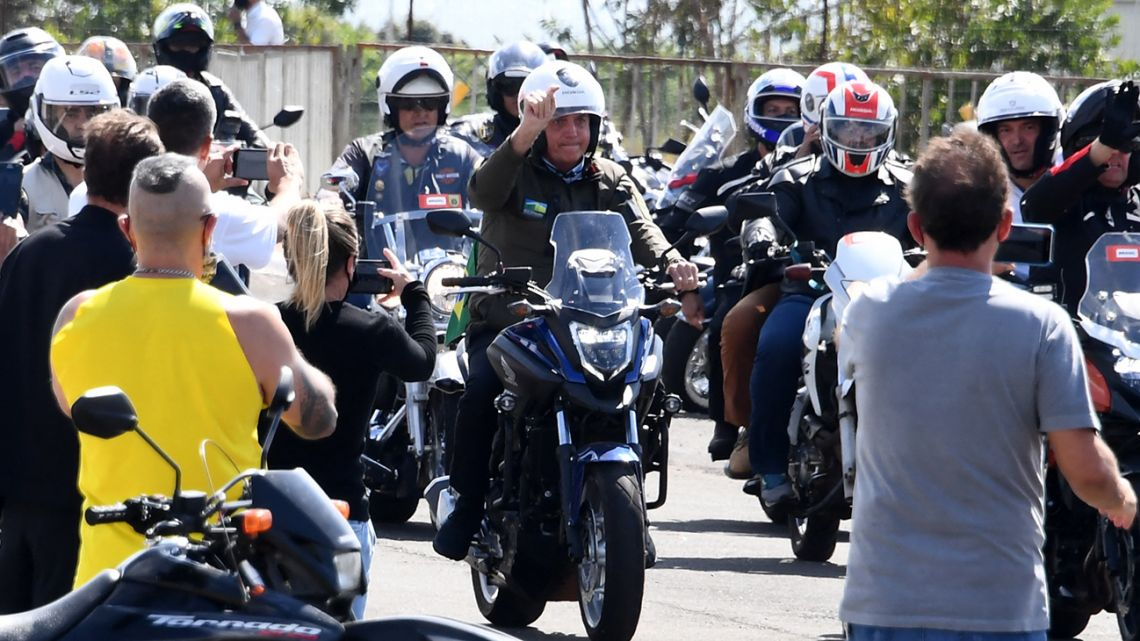 Brazil's President Jair Bolsonaro (C) rides a motorcycle as he leads a caravan of more than 1000 bikers to celebrate Mother's Day in Brasilia on May 9, 2021.