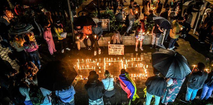 La gente rodea las velas encendidas colocadas formando el acrónimo S.O.S. durante una protesta contra el gobierno del presidente Iván Duque, en Medellín, Colombia.