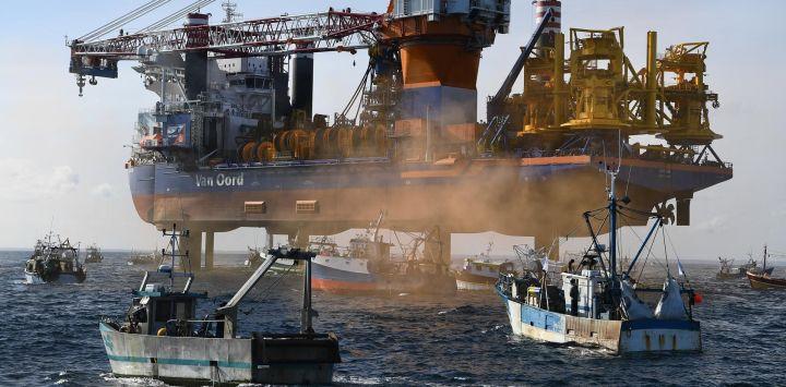 Barcos de pesca rodean el buque plataforma de perforación