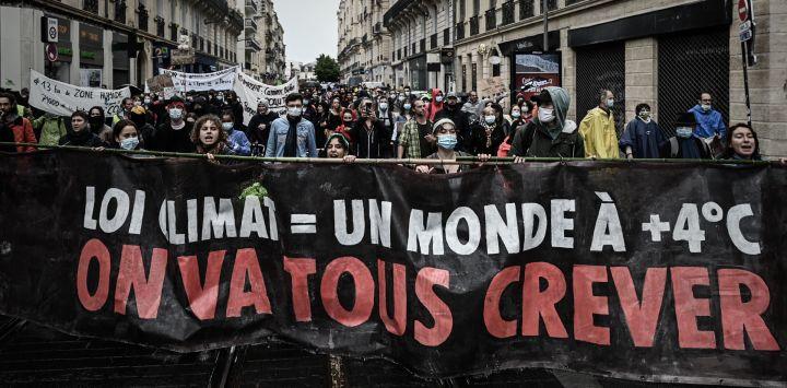 Activistas y manifestantes sostienen una pancarta que dice