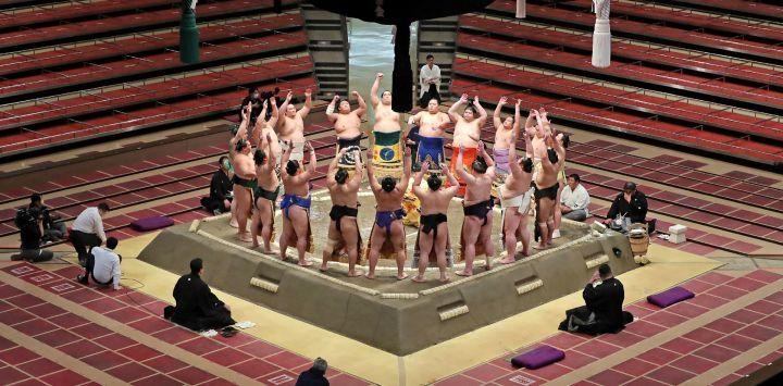 Los luchadores de sumo se reúnen en el ring y participan en un ritual antes de sus combates en el primer día de un nuevo torneo de sumo de 15 días en Tokio, sin espectadores debido al estado de emergencia del COVID-19 en Japón.