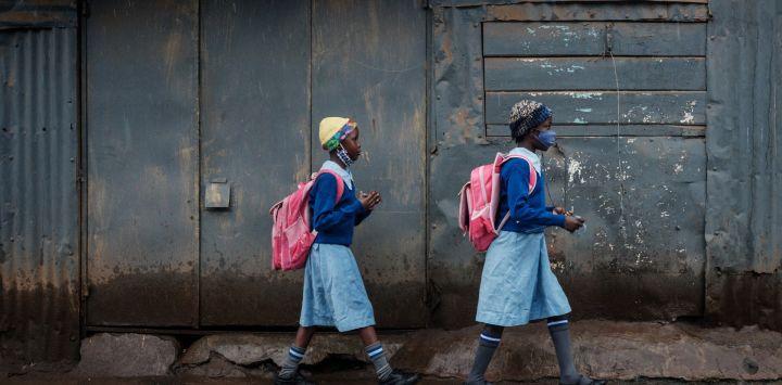 Los estudiantes caminan hacia la escuela primaria olímpica mientras las escuelas vuelven a abrir después de un receso de 6 semanas siguiendo la directiva del presidente de Kenia, Uhuru Kenyatta, de frenar la propagación del coronavirus Covid-19, en el barrio pobre de Kibera, Nairobi.
