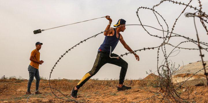 Un manifestante palestino utiliza una honda para arrojar piedras a las fuerzas de seguridad israelíes a lo largo de la valla fronteriza, al este de Khan Yunis en el sur de la Franja de Gaza.