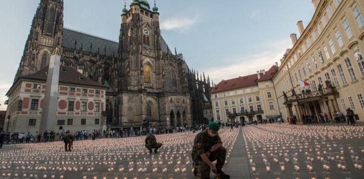 Un soldado enciende una vela para conmemorar a las víctimas de la pandemia COVD-19 en el Castillo de Praga en Praga.