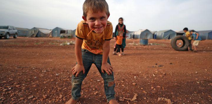 Un niño sirio posa para una foto mientras juega en un campamento para desplazados internos en la ciudad de Maaret Misrin, en la provincia de Idlib, noroeste de Siria.