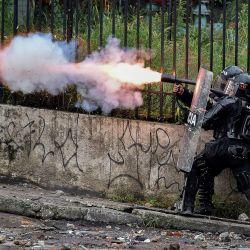 Un oficial de la policía antidisturbios lanza gases lacrimógenos a los manifestantes durante una protesta contra el gobierno en Cali, Colombia.   Foto:Luis Robayo / AFP