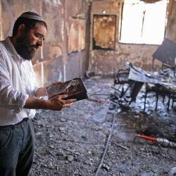 Un rabino inspecciona los daños dentro de una escuela religiosa incendiada en la ciudad central israelí de Lod, cerca de Tel Aviv, luego de los enfrentamientos nocturnos entre árabes israelíes y judíos israelíes en medio de una dramática escalada entre palestinos e israelíes provocada por disturbios en Jerusalén.   Foto:Ahmad Gharabli / AFP