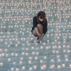 Una mujer enciende una vela para conmemorar a las víctimas de la pandemia COVD-19 en el Castillo de Praga.   Foto:Michal Cizek / AFP