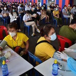 Los miembros del personal médico controlan los signos vitales de las personas antes de administrar dosis de la vacuna CoronaVac o AstraZeneca para el coronavirus Covid-19 fuera de un estadio de fútbol sala en Bangkok.   Foto:Lillian Suwanrumpha / AFP