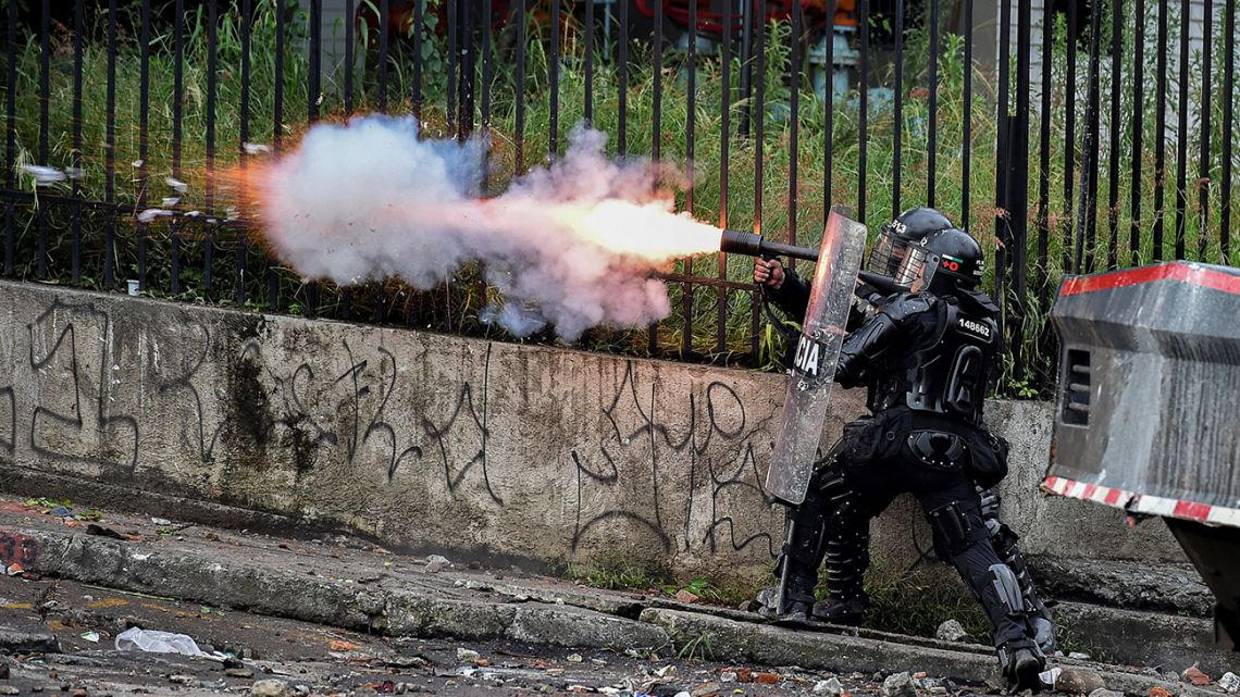 A riot police officer fires tear gas at demonstrators during a protest against the government in Cali, Colombia, on May 10, 2021.