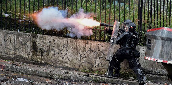 Un oficial de la policía antidisturbios lanza gases lacrimógenos a los manifestantes durante una protesta contra el gobierno en Cali, Colombia.