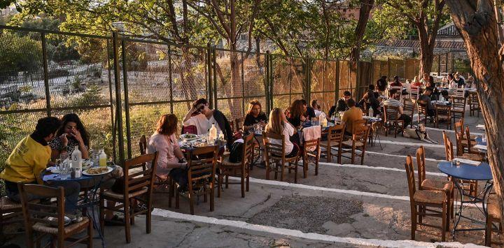 La gente se sienta en un café al aire libre junto al Ágora Antigua en Atenas, mientras Grecia alivia sus restricciones Covid-19, preparándose para abrir al turismo internacional el 14 de mayo.
