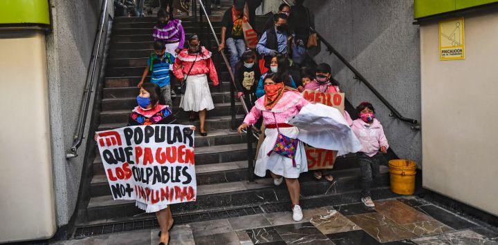 """Miembros de la etnia otomie con un cartel que decía """"Haz que paguen los culpables. No más impunidad """"participe en una protesta en demanda de justicia para las víctimas tras accidente de tren donde una línea elevada de metro colapsó parcialmente con vagones de tren, en la estación de metro Zapata, en la Ciudad de México."""