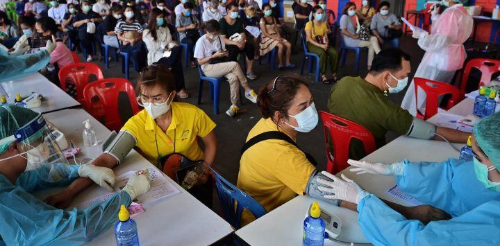 Los miembros del personal médico controlan los signos vitales de las personas antes de administrar dosis de la vacuna CoronaVac o AstraZeneca para el coronavirus Covid-19 fuera de un estadio de fútbol sala en Bangkok.